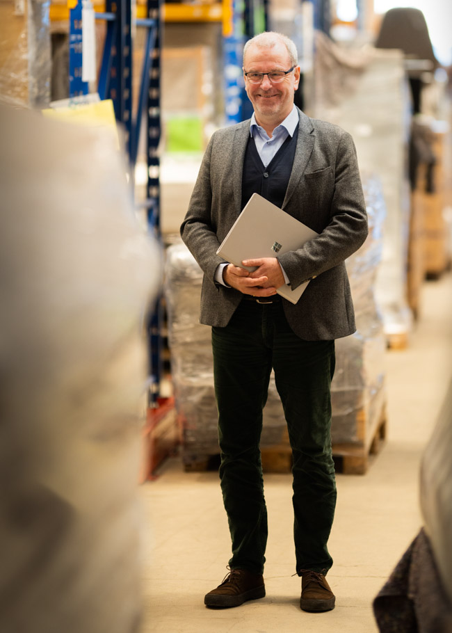 Jens Olesen Lund smiles in a warehouse